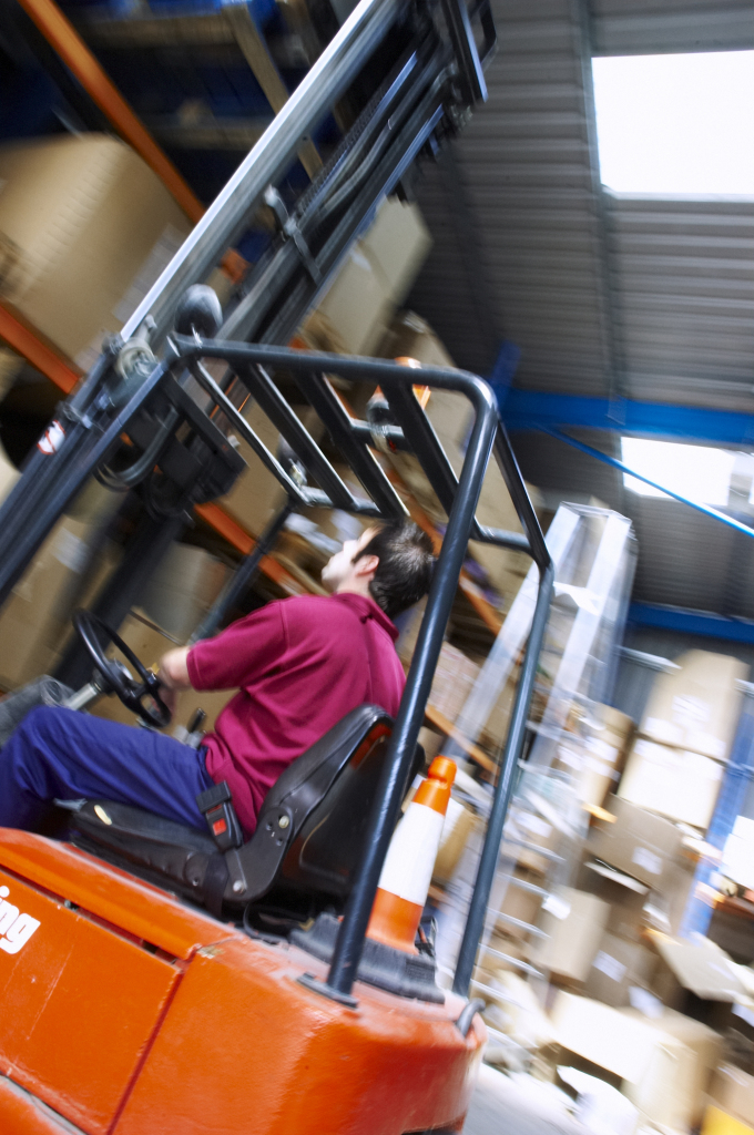 Fork-lift truck operating in the warehouse